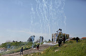 Palestinian protestors run for cover from tear gas fired by members of the Israeli security forces during clashes following a protest against closure...