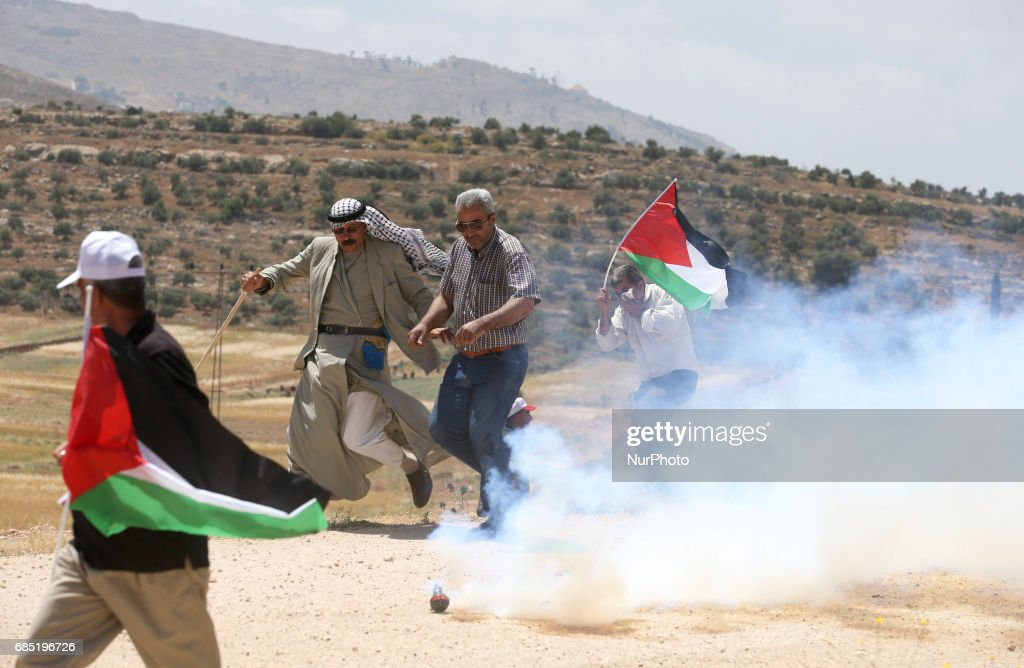 Palestinian protestors run for shelter from tear gas fired by Israeli soldiers during clashes at a protest in support of Palestinian prisoners on hunger strike in Israeli jails, in the West Bank village of Beit Dajan, near Nablus May 19, 2017.