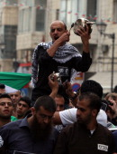 Palestinian protestors shout slogans and bang on pots covered in pictures of Palestinian prisoners Mahmoud alSarsak and Akram alRikhawi who are still...