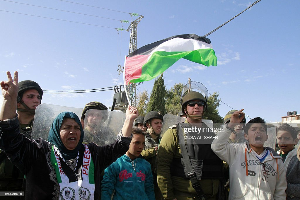 Palestinian protestors shout slogans in front of Israeli soldiers during a weekly demonstration against Israeli occupation in the West Bank village of Maasarah near Bethlehem on January 25, 2013. The Palestinian leadership wants new dialogue with Israeli political parties, particularly centrists who emerged strong in this week's election, an official said Thursday.