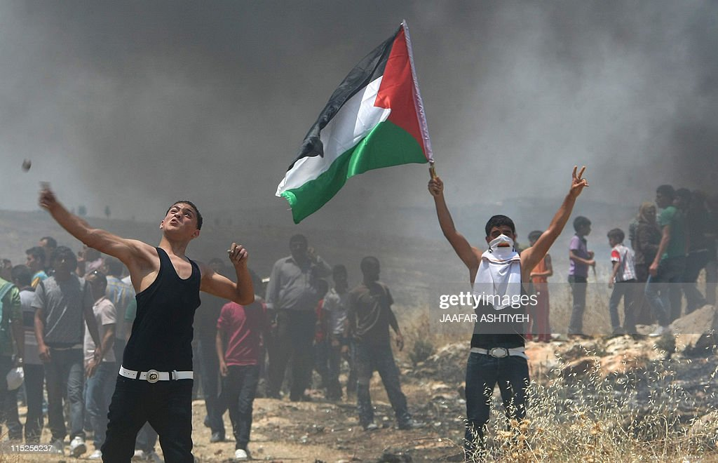 Palestinian protestors stand amidst smoke during clashes with Israeli forces following a demonstration against Israeli settlements in the West Bank...