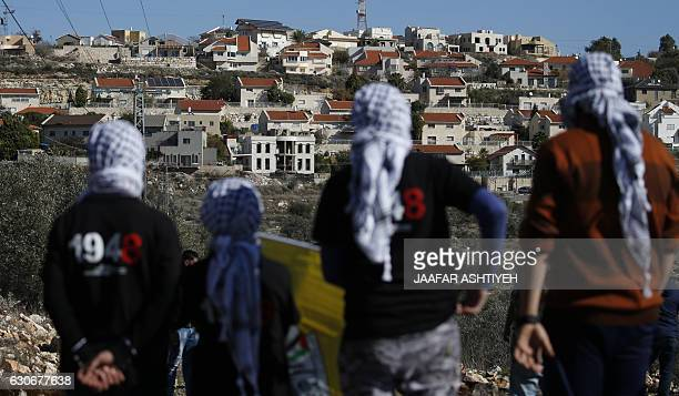 Palestinian protestors stand facing the Israeli settlement of Qadumim during clashes with Israeli security forces following a demonstration against...