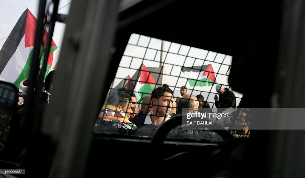 Palestinian protestors stand in front of an Israeli military vehicle during a protest in Anin village in the West Bank near Jenin city, on January 26, 2013. Protestors planned to erect a number of tents in solidarity with Palestinian prisoners in Israeli jails, a move they called 'Breaking the constraint'. AFP PHOTO/SAIF DAHLAH