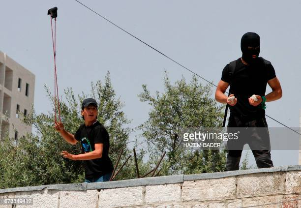 Palestinian protestors stand on top of a house in the West Bank city of Hebron on April 27 during clashes with Israeli soldiers as a trade strike in...