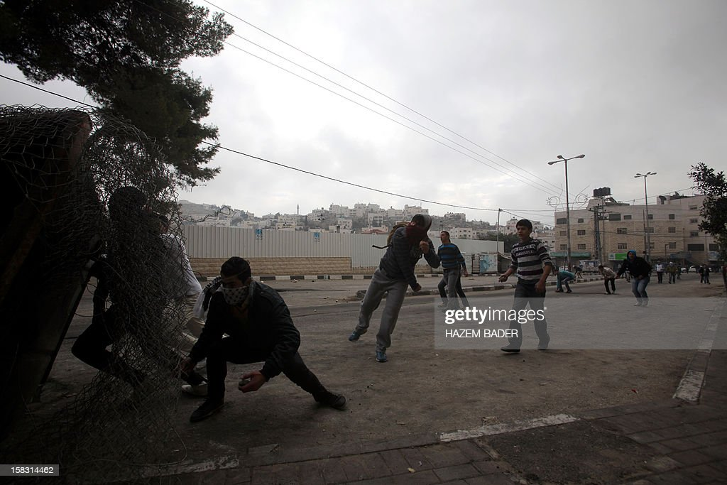 Palestinian protestors take cover behind a barricade as they throw stones at Israeli soldiers during clashes following the funeral of Mohamed Ziad Salayma on December 13, 2012, after he was killed the previous day by Israeli forces near his home in the old city of the West Bank town of Hebron. Thousands of Palestinians in Hebron mourned the death of the teenager who was shot after he allegedly threatened Israeli forces with a toy gun.