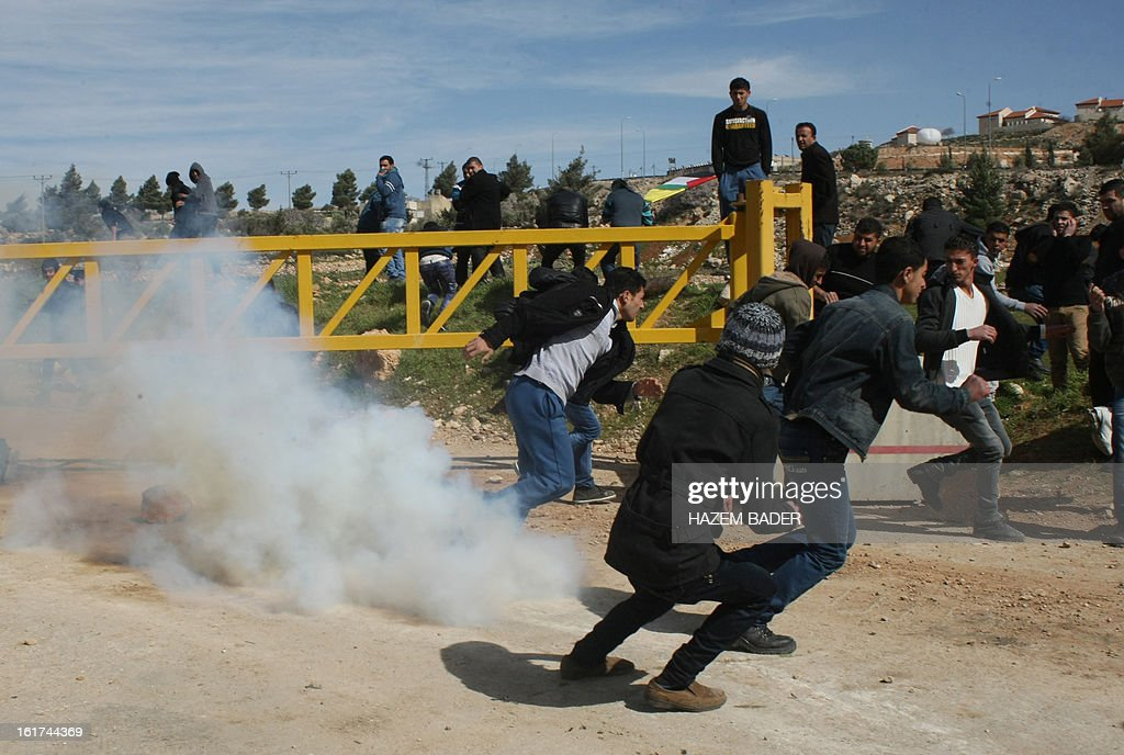 Palestinian protestors take cover from tear gas fired by Israeli security forces during a demonstration against the closer of the main southwest entrance of the West Bank city of Hebron, which is situated near the Jewish settlement of Beit Hagai, in the occupied West Bank, on February 15, 2013.