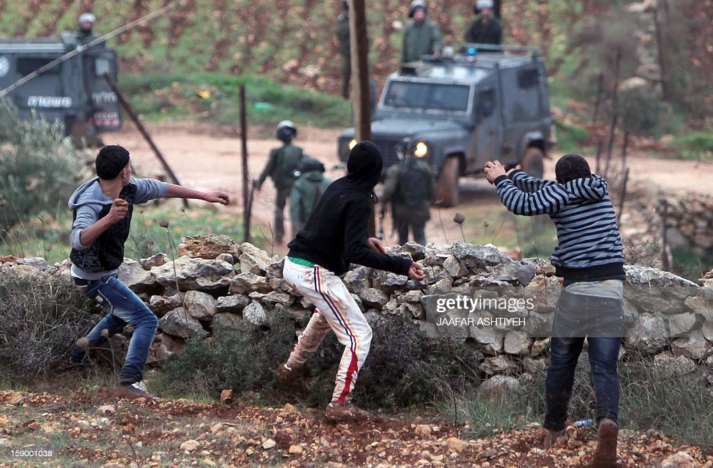Palestinian protestors throw stones at Israeli security forces during clashes in the northern village of Qusra, south of the city of Nablus, in the Israeli occupied West Bank, after Jewish settlers from the nearby Esh Kodesh outpost used the cover of fog to approach Qusra with the aim of uprooting dozens of olive saplings, but were confronted by Palestinian farmers who threw stones at them, on January 5, 2013. AFP PHOTO/JAAFAR ASHTIYEH