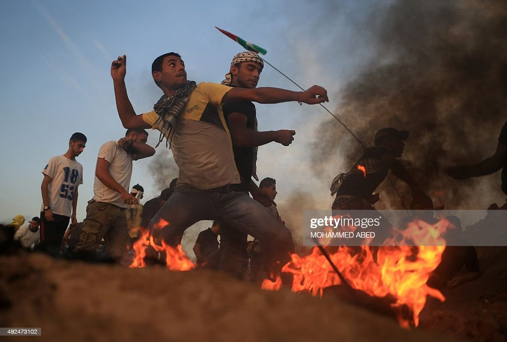 Palestinian protestors throw stones at Israeli soldiers during clashes after tearing down a section of a border fence between Israel and the central...