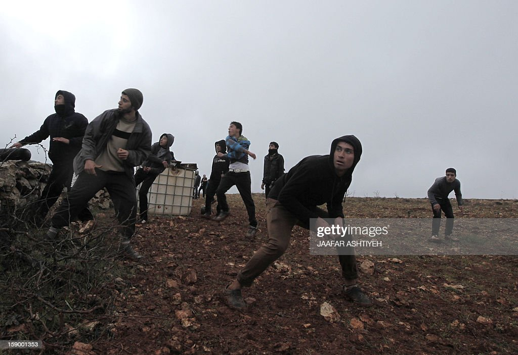 Palestinian protestors throw stones at Israeli soldiers in the northern village of Qusra, south of the city of Nablus, in the Israeli occupied West Bank, after Jewish settlers from the nearby Esh Kodesh outpost used the cover of fog to approach Qusra with the aim of uprooting dozens of olive saplings, but were confronted by Palestinian farmers who threw stones at them, on January 5, 2013. AFP PHOTO/JAAFAR ASHTIYEH