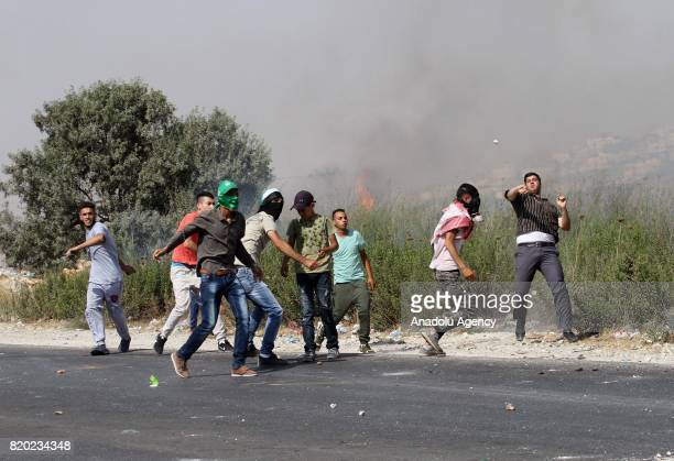 Palestinian protestors throw stones in response to Israeli security forces' intervention with tear gas bomb during a demonstration to protest Israeli...