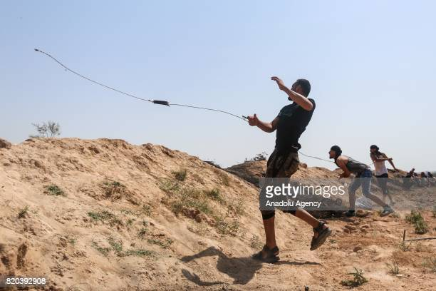 Palestinian protestors throw stones in response to Israeli security forces' intervention during a demonstration to protest Israeli violations and...