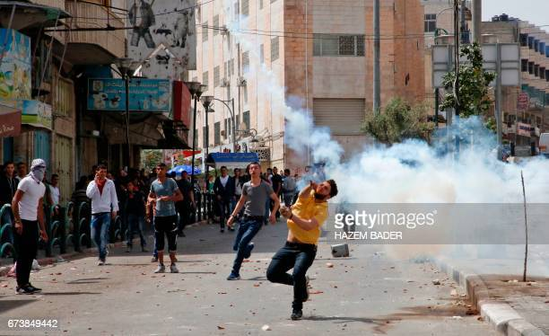 Palestinian protestors throw stones in the West Bank city of Hebron on April 27 during clashes with Israeli soldiers as a trade strike in support of...