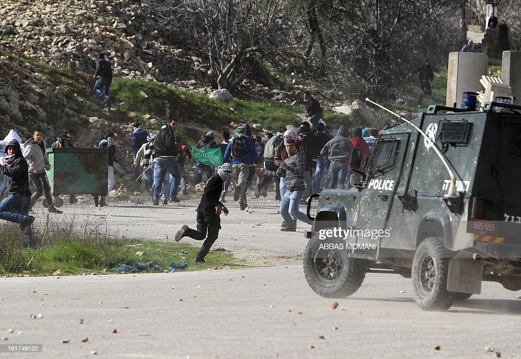 Palestinian protestors throw stones towards an Israeli police vehicle during clashes in front of Ofer prison, near the West Bank city of Ramallah, following a demonstration in support of Palestinian detainee, Samer Issawi, who has been on hunger strike for more than 200 days, and other prisoners on hunger strike in Israeli prisons on February 15, 2013. A United Nations official on February 13, expressed concern about the wellbeing of Palestinian detainees in Israeli prisons and in particular about the condition of Issawi. AFP PHOTO/ABBAS MOMANI