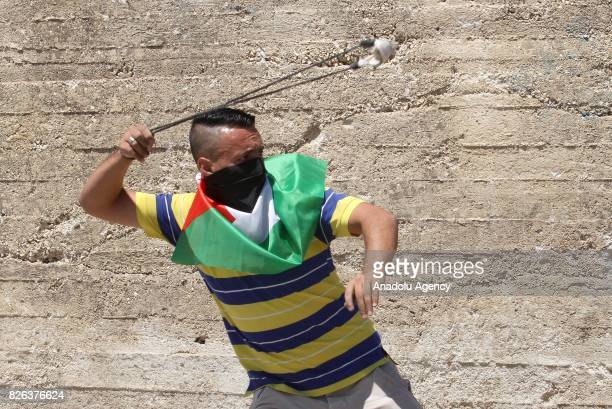 Palestinian protestors throw stones towards Israeli security forces during clashes following a demonstration against the recent Israeli restrictions...