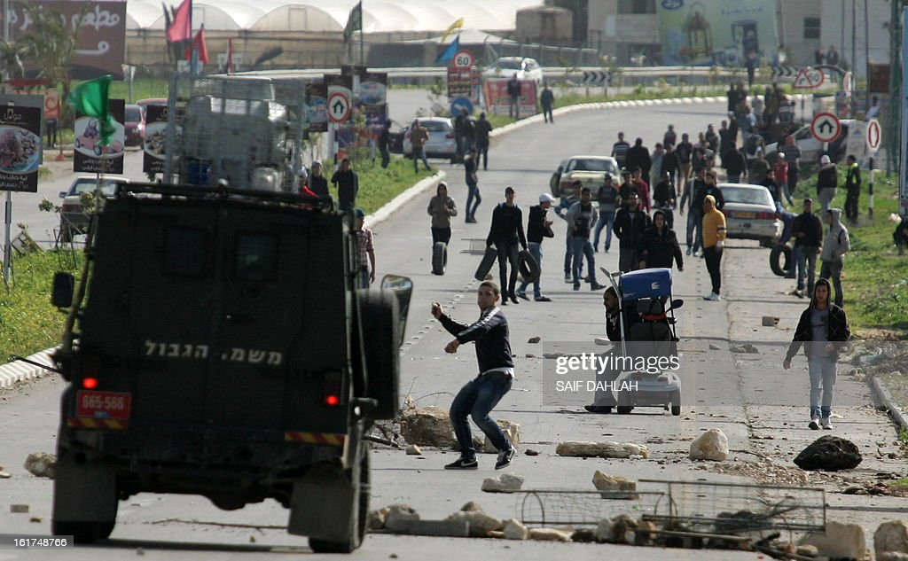 Palestinian protestors throw stones towards Israeli security froces during clashes at the entrance of the Jalama checkpoint, near the West Bank city of Jenin, on February 15, 2013. AFP PHOTO/SAIF DAHLAH