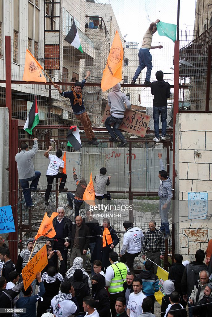 Palestinian protestors try to place the national flag atop the fence in al-Shuhada street in the West Bank town of Hebron on February 22, 2013 during a protest demanding the right of access for Palestinians to the street that can only be used by Israeli settlers.