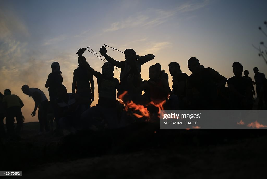 Palestinian protestors use sling shots to throw stones at Israeli soldiers after tearing down a section of a border fence between Israel and the Gaza...