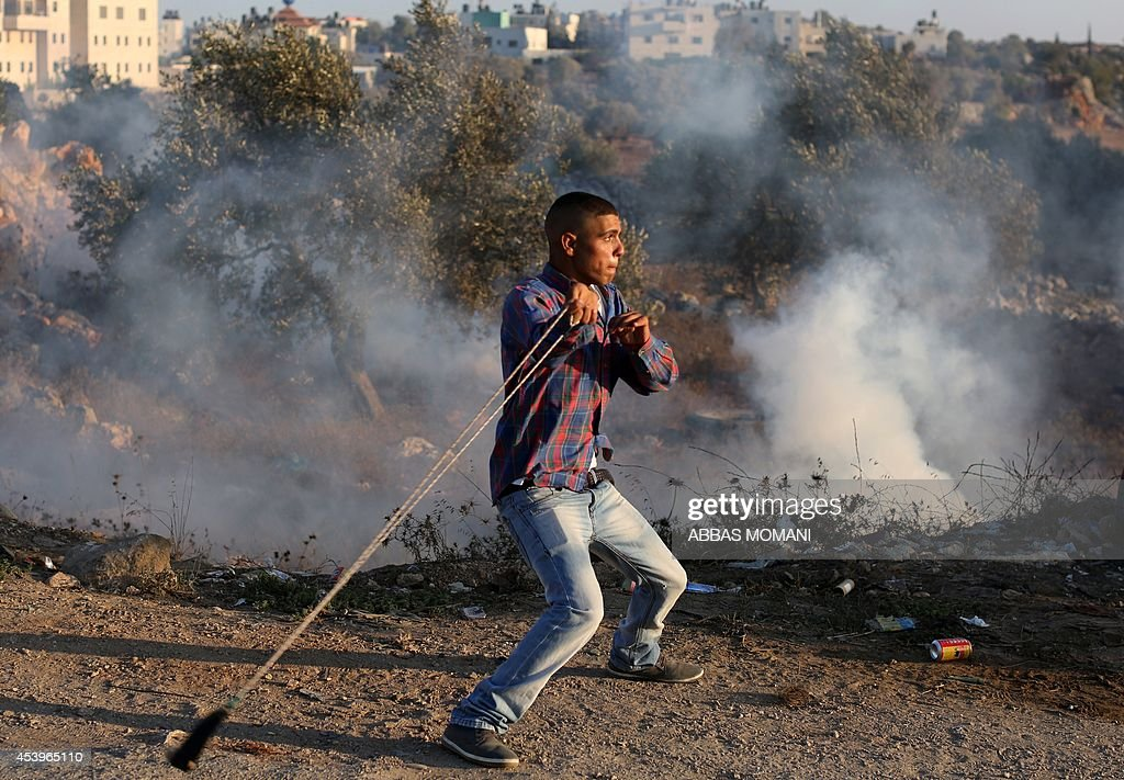 A Palestinian protestors uses a sling shot to throw stones towards Israeli security forces during clashes in the West Bank village of Silwad, near Ramallah, following a demonstration in support of the Hamas militants' resistance in the Gaza Strip and against the killing of children by Israeli strikes on the Palestinian enclave on August 22, 2104. Hamas gunmen executed 18 people accused of collaborating with Israel in Gaza City as Palestinian mortar fire killed a four-year-old Israeli boy on Day 46 of a devastating war. AFP PHOTO / ABBAS MOMANI