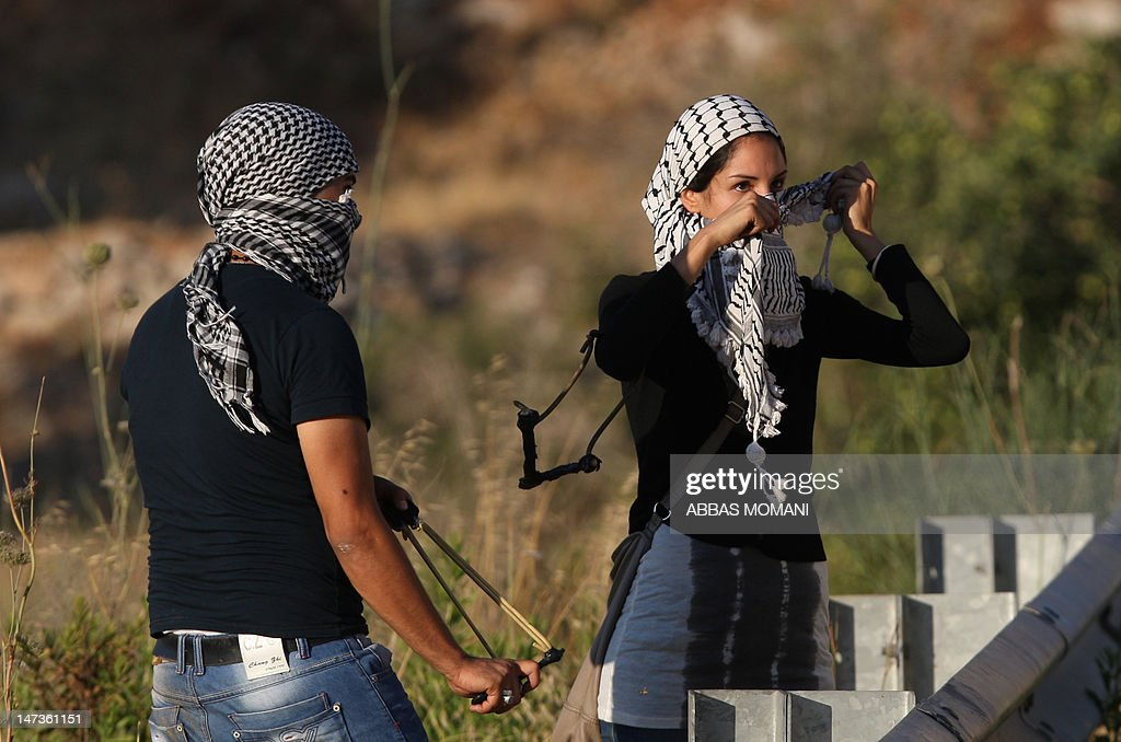 Palestinian protestors using slingshots cover their faces with the traditional chequerred keffiyeh during clashes with Israeli troops following a demonstration on June 28, 2012 outside the Ofer military prison in the occupied West Bank, near Ramallah, in solidarity with Palestinian prisoners being held in Israeli jails. More than 1,500 Palestinian prisoners ended a mass hunger strike in support of demands for better conditions in a deal with prison authorities in May with one of the terms of the agreement being that those held without trial in what Israel calls 'administrative detention' would go free at the end of their current term -- unless fresh evidence emerged against them.