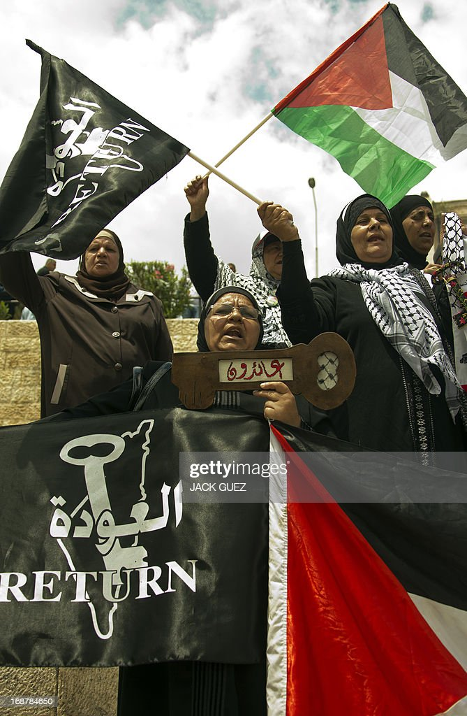 Palestinian protestors wave their national flag and flags bearing the word: 'Return' during a rally outside Damascus gate in Jerusalem on May 15, 2013 to mark the 65th Nakba or 'catastrophe' of the Jewish state's creation in 1948, during which 760,000 Palestinians fled their homes. Thousands of Palestinians took to the streets in the West Bank and the Gaza Strip to demonstrate on Nakba Day and assert their 'right to return' to where their ancestors fled after the Israeli victory over Arab armies.