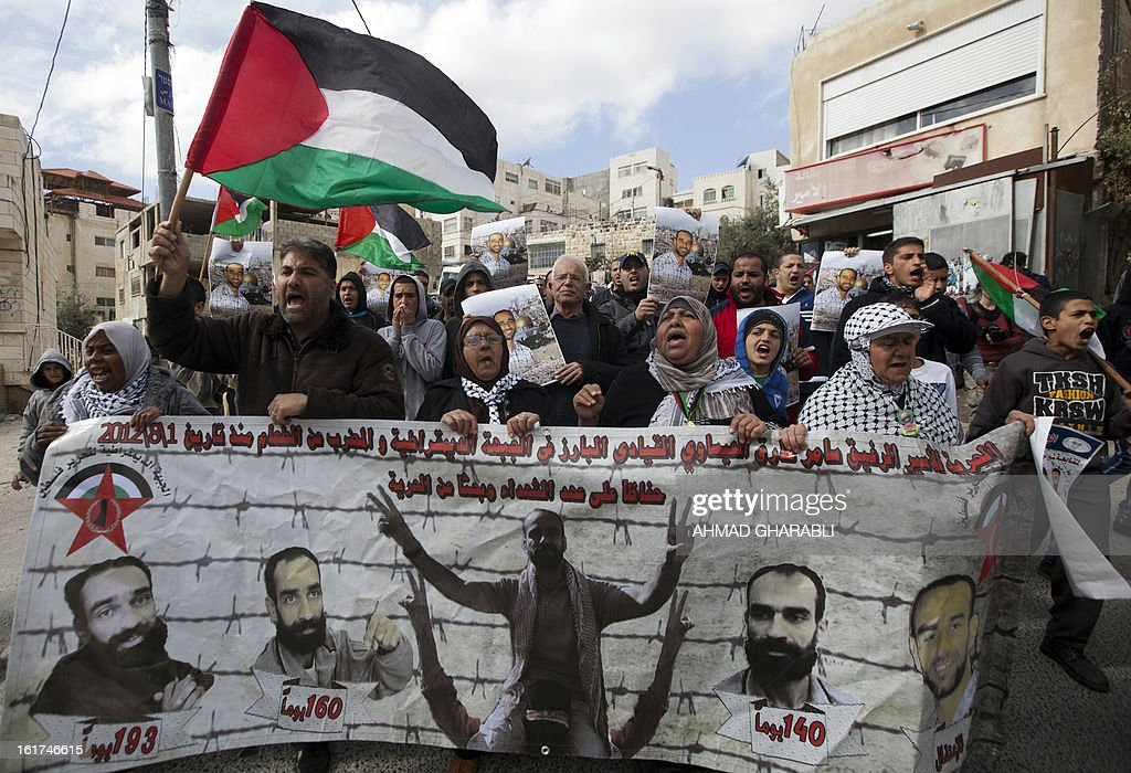 Palestinian protestors wave their national flag and hold portraits of Samer Issawi, a Palestinian prisoner who has been on hunger strike for more than 200 days in an Israeli pirson, during a demonstration demanding for his release in the Arab east Jerusalem neighbourhood of Issawiya on February 15, 2013. A United Nations official on February 13, expressed concern about the wellbeing of Palestinian detainees in Israeli prisons and in particular about the condition of Issawi.
