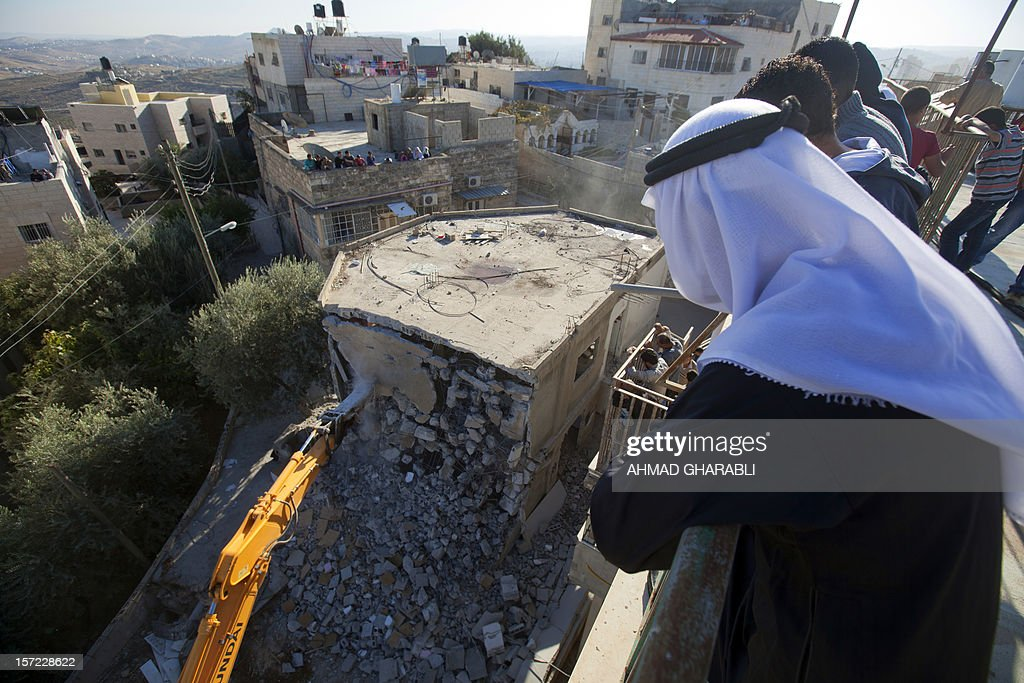 Palestinian Rafet Dabash looks at a bulldozer destroying his own home in the east Jerusalem district of Sur Baher on November 30, 2012 after an Israeli court ruled that the house was built without a municipality permit. Many Palestinians end up demolishing their homes themselves to avoid the high cost of paying for Israeli government bulldozers, or going to prison for not being able to pay. Israel is to build 3,000 new settler homes in east Jerusalem and the West Bank after the Palestinians won recognition as a non-member state at the United Nations, an Israeli official said today. AFP PHOTO / AHMAD GHARABLI