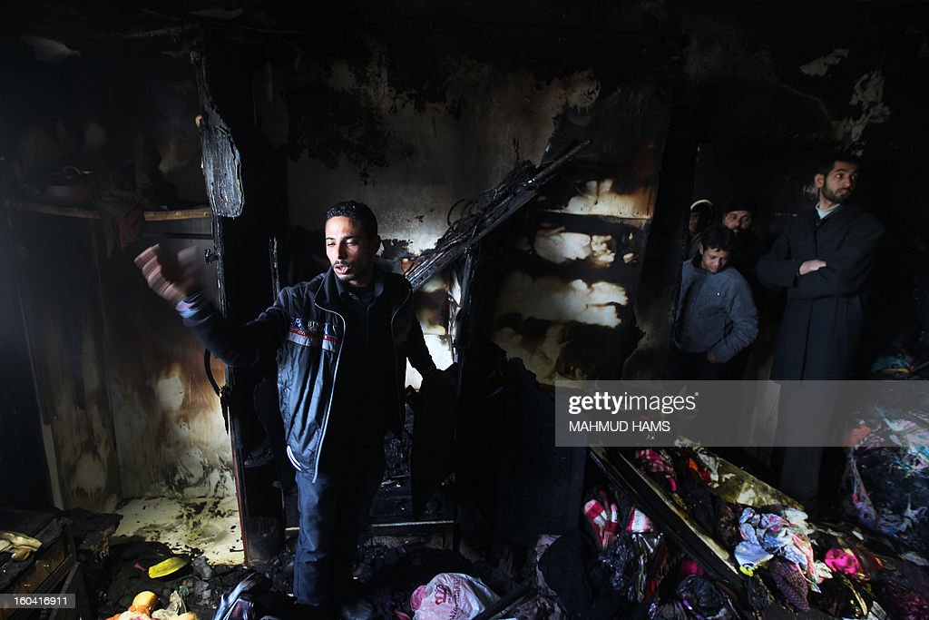 Palestinian Ramadan Dheir (L) and other people inspect a burnt room after a fire swept over his brother's house in Gaza City on January 31, 2013. Hazem Dheir, his wife Sahar and their four young children were killed in the fire that is believed to have started by an electrical fault.