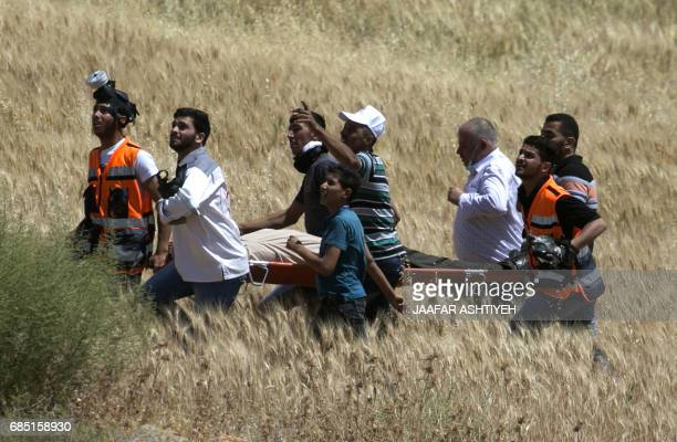 Palestinian Red Crescent paramedics carry an injured demonstrator on a stretcher during clashes with Israeli forces following a protest in support of...