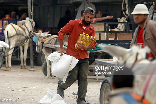A Palestinian refugee carries food supplies handed out at the United Nations Relief and Works Agency food distribution center in the town of Rafah in...