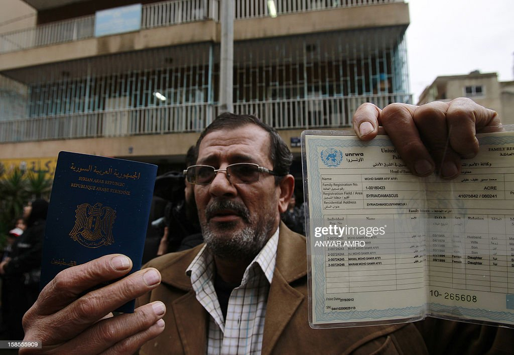 A Palestinian refugee from the Syrian refugee camp of Yarmuk holds up his passport in front of the United Nations Relief and Works Agency (UNRWA) offices in the Cola district of the Lebanese capital, Beirut, on December 19, 2012. More than 2,000 Palestinians from the Yarmuk camp, on the southern outskirts of Damascus, have fled battles pitting rebels against pro-regime fighters for neighbouring Lebanon. AFP PHOTO / ANWAR AMRO