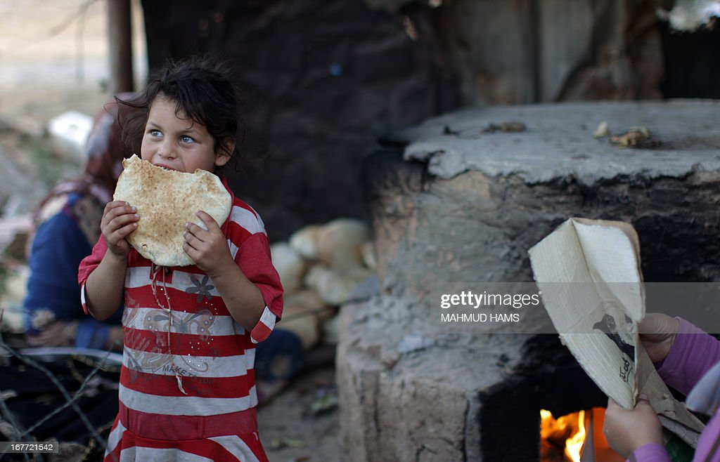 A Palestinian refugee girl eats freshly baked bread in a poverty-stricken quarter of the town of Beit Lahia, in the northern Gaza Strip, on April 28.2013.