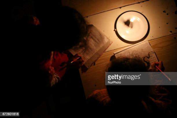 Palestinian refugee girls study by candlelight in their family's makeshift house during a power outage at Khanyounis refugee camp in the southern...