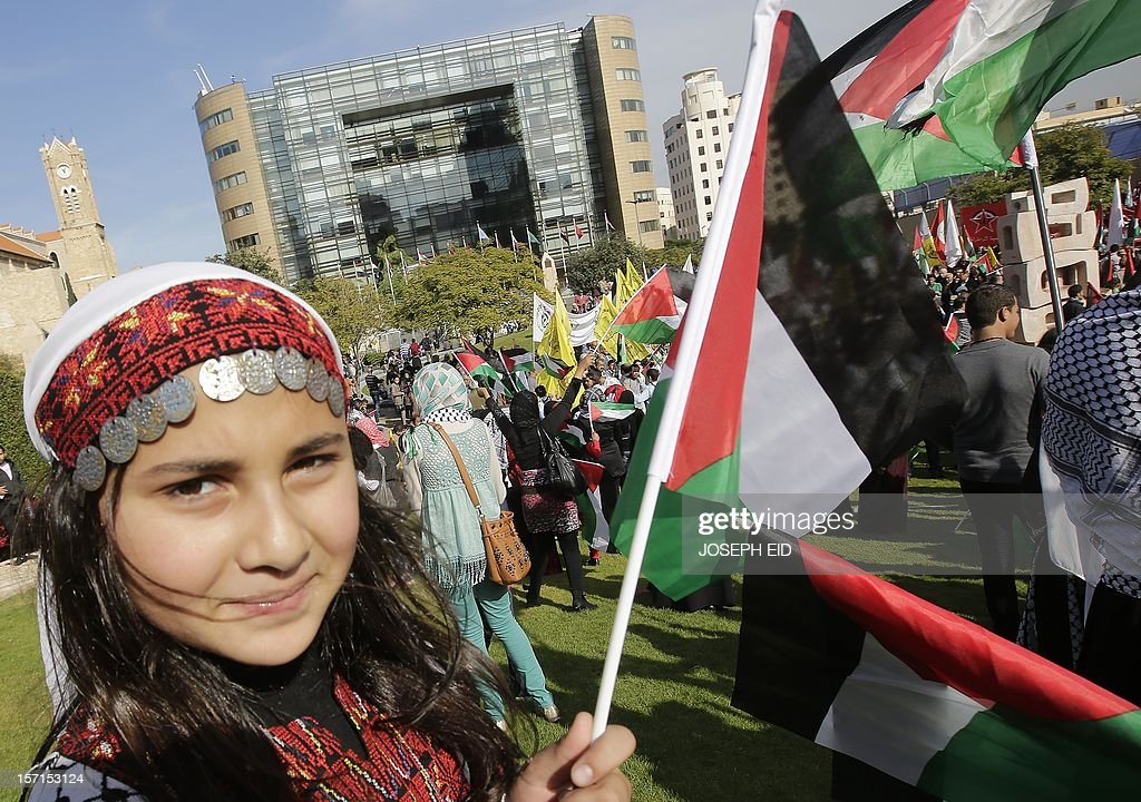 A Palestinian refugee in Lebanon waves her national flag during a gathering outside the United Nations headquarters in Beirut on November 29, 2012 in support of Palestinian leader Mahmud Abbas which is heading to the General Assembly today with huge backing for his bid for UN recognition of statehood despite strong US and Israeli opposition. Abbas will make the case for Palestine to become a UN 'non-member observer state' and indicate his conditions for talks with Israel in a key speech to the 193-member assembly. AFP PHOTO / JOSEPH EID