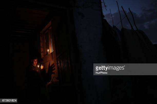 A Palestinian refugee man uses candle as light source in his makeshift house during a power outage at Khanyounis refugee camp in the southern Gaza...