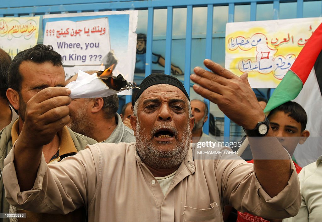 A Palestinian refugee threatens to set himself on fire during a protest outside the offices of the United Nations Relief and Works Agency (UNRWA) in Gaza city on April 8, 2013 to demand resumption of food deliveries to refugees, stopped last week after dozens of Gazans stormed a UN depot, demanding reinstatement of a monthly cash allowance to poor families which was halted from April 1 due to budget cuts. Gaza's Hamas rulers urged the UN on April 5 to reconsider its suspension of food aid for Palestinian refugees.