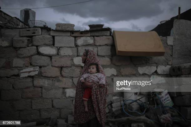 A Palestinian refugee woman carries her baby in their makeshift house at Khanyounis refugee camp in the southern Gaza Strip 23 April 2017 With high...