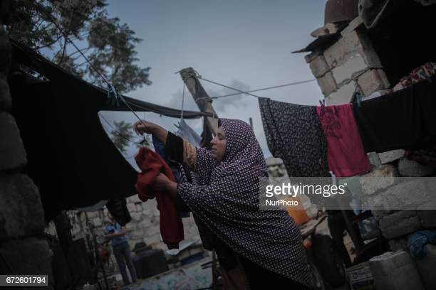 A Palestinian refugee woman washes clothes near a fire during a power outage at Khanyounis refugee camp in the southern Gaza Strip 23 April 2017 Most...