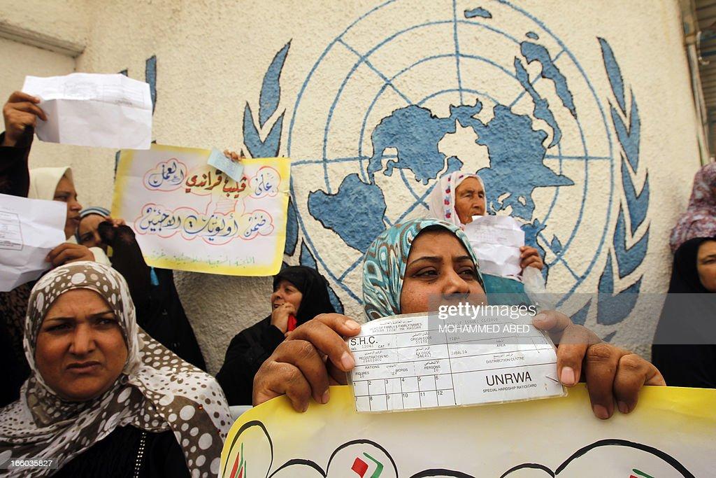 Palestinian refugee wp,em protest outside the offices of the United Nations Relief and Works Agency (UNRWA) in Gaza city on April 8, 2013 to demand resumption of food deliveries to refugees, stopped last week after dozens of Gazans stormed a UN depot, demanding reinstatement of a monthly cash allowance to poor families which was halted from April 1 due to budget cuts. Gaza's Hamas rulers urged the UN on April 5 to reconsider its suspension of food aid for Palestinian refugees.