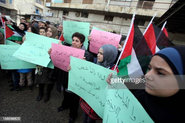 Palestinian refugees from the Syrian refugee camp of Yarmuk carry placards as they gather during a protest in the Palestinian Beddawi refugee camp in...