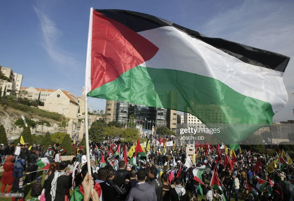 Palestinian refugees in Lebanon wave national flags during a gathering outside the United Nations headquarters in Beirut on November 29, 2012 in support of Palestinian leader Mahmud Abbas which is heading to the General Assembly today with huge backing for his bid for UN recognition of statehood despite strong US and Israeli opposition. Abbas will make the case for Palestine to become a UN 'non-member observer state' and indicate his conditions for talks with Israel in a key speech to the 193-member assembly. AFP PHOTO / JOSEPH EID