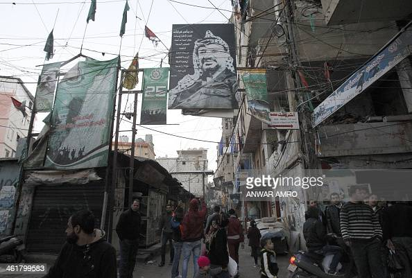 Palestinian refugees living in the the Shatila refugee camp in the Lebanese capital Beirut walk under a banner of the late president Yasser Arafat on...