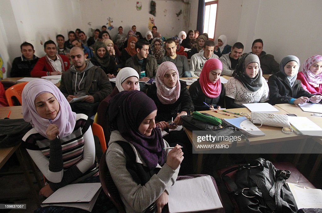 Palestinian refugees, some of whom fled the Yarmuk refugee camp in Damascus, attend class in the 'Palestine' Palestinian refugee camp in the Syrian city of Homs on January 21, 2013. Syrian warplanes launched raids on two towns east of Damascus, a monitoring group said, as a total overnight electricity blackout in the capital began to lift in the morning. AFP PHOTO/ANWAR AMRO