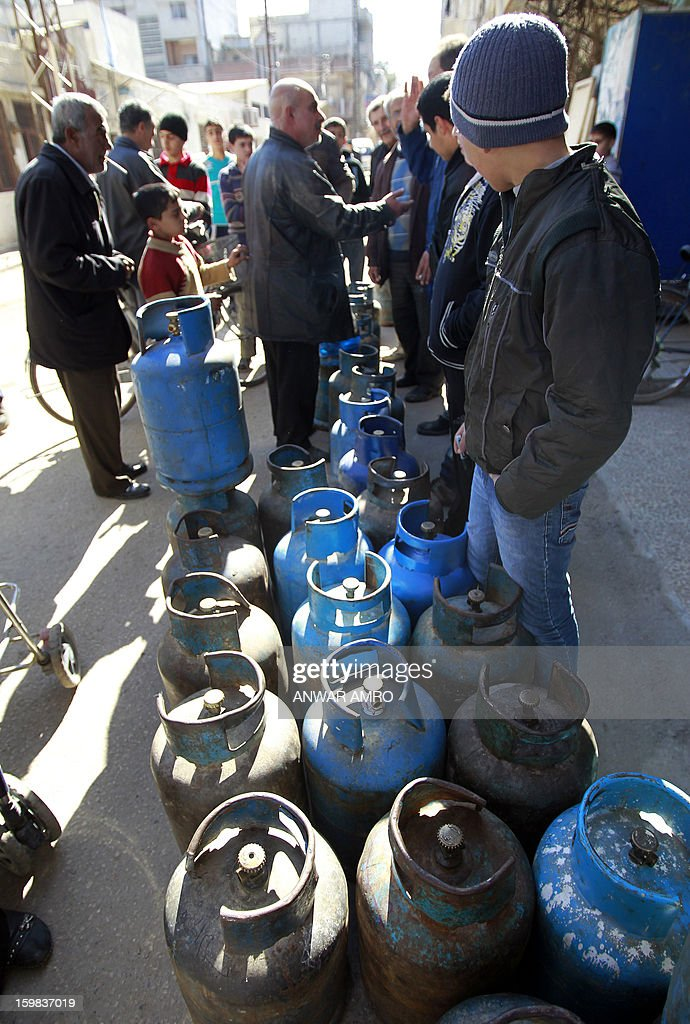 Palestinian refugees wait to fill and collect gas bottles at the 'Palestine' Palestinian refugee camp in the Syrian city of Homs, on January 21, 2013, as the country suffers from a lack of commodities including petrol, diesel for heating homes and flour. The Syrian authorities have raised the prices of petrol, wheat and flour, state media said, three days after the price of diesel was hiked amid a severe economic crisis in the war-torn country.