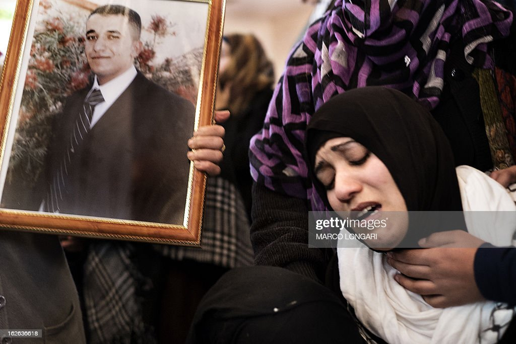 A Palestinian relative of Arafat Jaradat, who died in an Israeli prison, mourns next to his picture during his funeral in the West Bank village of Saair on February 25, 2013. Militants of the Al-Aqsa Martyrs Brigades, the armed wing of Palestinian president Mahmud Abbas' Fatah movement, vowed to avenge the death of Jaradat, a prisoner they say was tortured in an Israeli jail.