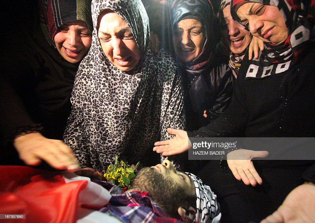 Palestinian relatives and friends mourn during the funeral of Anas al-Atrash, 23, who was killed by Israeli soldiers at a checkpoint near Jerusalem, on November 8, 2013, in the West Bank city of Hebron. Israeli border police shot dead the Palestinian man at a checkpoint around midnight (2200 GMT), when the man ran at a border police officer with a knife, prompting him to open fire, Israeli police said. This is the second fatal shooting by Israeli forces in 12 hours.