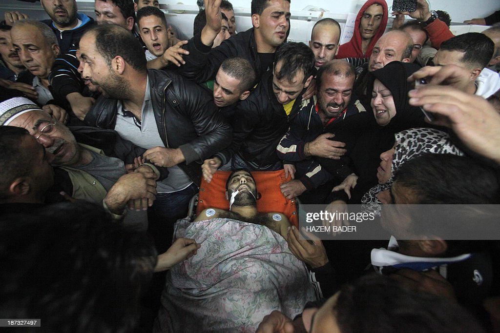Palestinian relatives and friends mourn over the body of Anas al-Atrash, 23, after he was killed by Israeli soldiers at a checkpoint near Jerusalem, on November 8, 2013, in the West Bank city of Hebron. Israeli border police shot dead the Palestinian man at a checkpoint around midnight (2200 GMT), when the man ran at a border police officer with a knife, prompting him to open fire, Israeli police said. This is the second fatal shooting by Israeli forces in 12 hours.