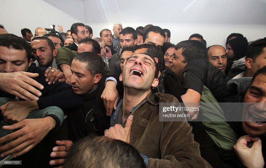 Palestinian relatives and friends mourn over the death of Arafat Jaradat, who died in an Israeli prison, after his body was handed over by Israeli authorities on February 24, 2013 at a hospital in ...
