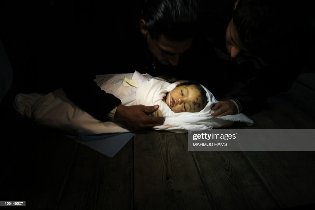 Palestinian relatives mourn over the body of Hanen Tafesh, a 10-month-old girl, at the morgue of the al-Shifa hospital in Gaza City, on November 15, 2012, after she died of wounds following an Israeli strike in the Zeitun neighbourhood. Several Palestinians and Israelis were killed in a wave of unrelenting cross-border fighting as the Jewish state pressed a vast air offensive on Gaza.