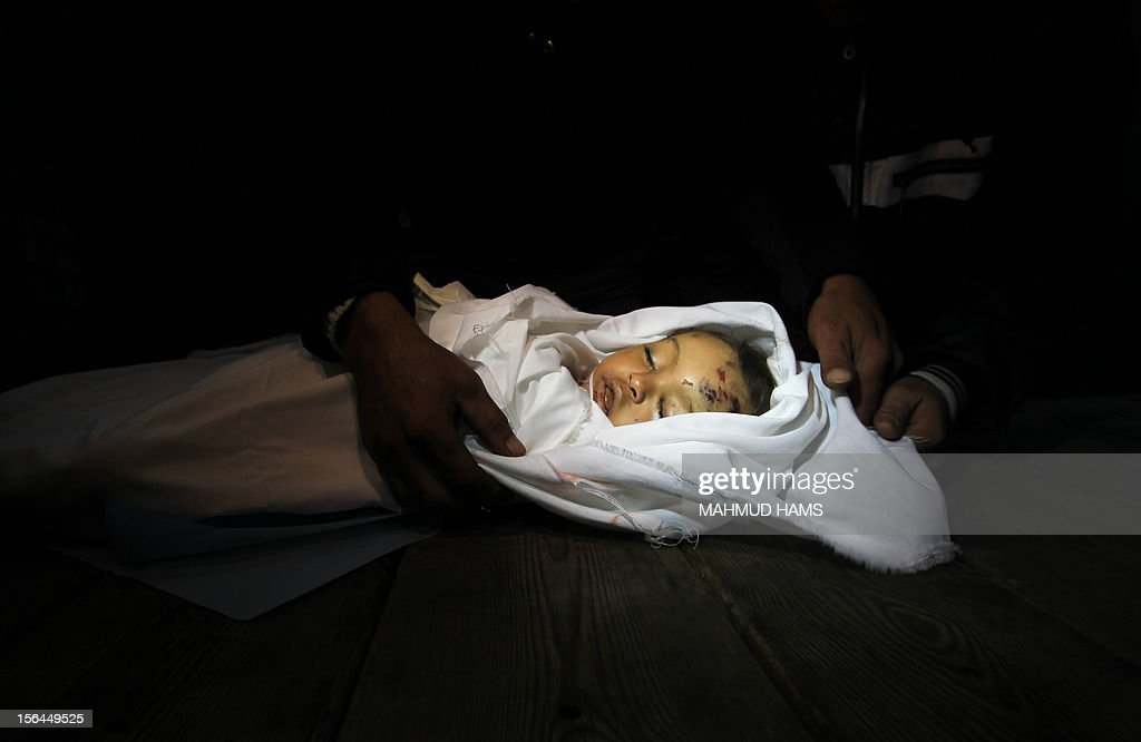 Palestinian relatives mourn over the body of Hanen Tafesh, a 10-month-old girl, at the morgue of the al-Shifa hospital in Gaza City, on November 15, 2012, after she died following an Israeli air strike in the Zeitun neighbourhood. Several Palestinians and Israelis were killed in a wave of unrelenting cross-border fighting as the Jewish state pressed a vast air offensive on Gaza.