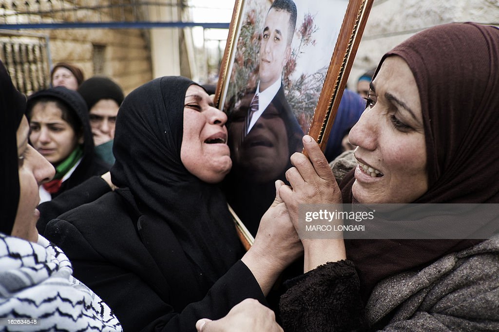 Palestinian relatives of Arafat Jaradat, who died in an Israeli prison, hold his picture as they mourn during his funeral in the West Bank village of Saair on February 25, 2013. Militants of the Al-Aqsa Martyrs Brigades, the armed wing of Palestinian president Mahmud Abbas' Fatah movement, vowed to avenge the death of Jaradat, a prisoner they say was tortured in an Israeli jail.